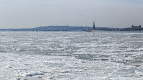 View of the Statue of Liberty and Jersey City across the frozen Hudson River Royalty Free Stock Images