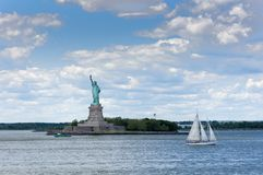 View of the Statue of Liberty in New York City, with a tugboat in the Hudson River stock photo