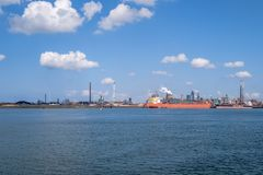 View on the steel plant in IJmuiden, Netherlands. Orange bulk carrier brings a new load of iron ore for the steel plant Stock Photo