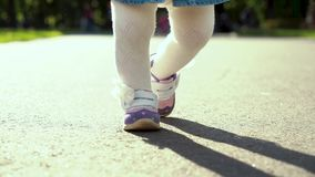 View of stepping feet of toddler girl walking in sunny park with parents stock video footage