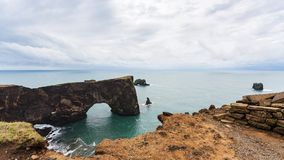 View of stone arch on Dyrholaey cliff in Iceland. Travel to Iceland - view of stone arch on Dyrholaey cliff near Vik I Myrdal village on Atlantic South Coast in Stock Image