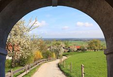 View through stone arch, rural spring landscape. View through stone arch, rural landscape with blossoming apple tree and walkway Royalty Free Stock Images