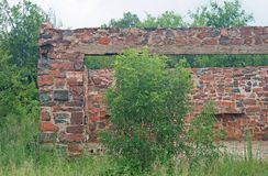 STONE WALL STRUCTURE OF HOUSE IN RUINS IN NATURE. View of a stone built wall forming part of the ruins of an old stone cottage Stock Photography