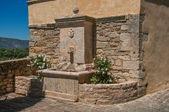 View of stone fountain with flowers and sunny blue sky, at the village of Ménerbes. Royalty Free Stock Photography