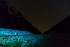 View of Stone rural Building in Nepal Mountains at Night. View of Stone rural Building in Nepal Mountains at Nigh and Night starry Sky rocky Ridges on Background Stock Photo