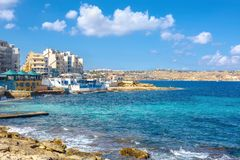 Stone coast and apartments houses in Bugibba district. Malta. View of stone shore and seaside buildings in Bugibba district. Malta Stock Photography