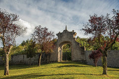 View of stone wall and gate at sunset amidst the vegetation in the Park of Bomarzo. View of stone wall and gate at sunset amidst the vegetation in the Park of Stock Photography