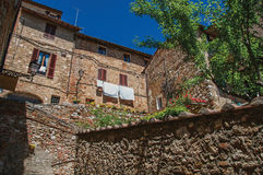 View of stone wall, old buildings with flowering plants at Colle di Val d`Elsa. View of stone wall, old buildings with flowering plants and blue sky at Colle di Stock Photos