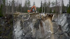 Excavation work on a rock in Karelia. View of stones falling into the amarble quarry in Karelia on a spring cloudy day stock video
