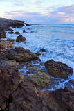 View of Stones and waves with foam at the a rocky coast of sea in the evening Royalty Free Stock Photography
