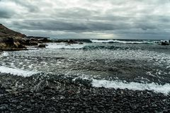 View from a stony deserted  shore to the stormy ocean stock image