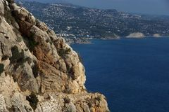 View of the stony path at the edge of the mountain, below the blue sea.  stock images