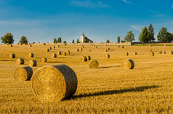 Romantic view of straw bales field. Sunlit summer landscape after a harvest of grain with a church and a churchyard on the horizon. Scenic rural background of royalty free stock photography