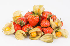 View of strawberries with green leaves and yellow golden physalis. Royalty Free Stock Photo