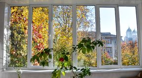 View of the street from the verandas with metal-plastic windows. View of the street and autumn landscape from the verandas with metal-plastic windows Royalty Free Stock Image