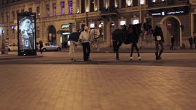View of street with crossroad, advert screen and two person with horses. Night stock video footage