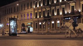 View of street with crossroad, advert screen and two person on horses. Night. View of street with buildings, crossroad, traffic light, parked cars, advert screen stock footage
