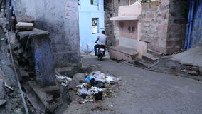 View of street in Jodhpur while man on the�motorcycle passes by. stock footage