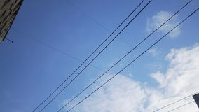 View of street lights and wires, for supplying power to the city trolley bus near the building against a blue cloudy sky royalty free stock photo
