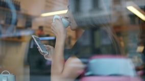 View from the street of a young lady with long hair messaging using her mobile phone and drinking her tea or coffee from stock video footage