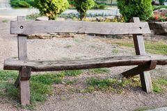 View of stylish wooden beanch in park. View of stylish wooden brown beanch in park. Garden furniture for family and company Royalty Free Stock Image