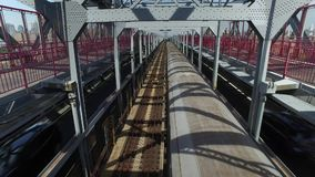 View of Subway Train Traveling on Williamsburg Bridge. A unique perspective of looking down at a subway train as it passes directly underneath a pedestrian on stock video footage