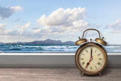 View of summer sea under blue sky. From window with alarm clock Royalty Free Stock Photo