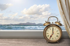 View of summer sea under blue sky. From window with alarm clock and curtain Stock Photography