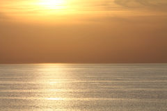 View on sun above ocean in orange sunset with texture reflection in water Stock Photo