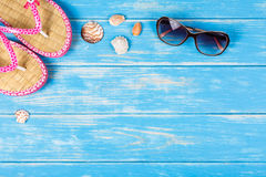 View of sunglasses seashells and flip-flops lying on blue wooden background. Royalty Free Stock Images