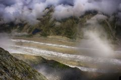 View on sunlit glacier through the clouds Royalty Free Stock Photo