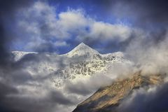 View on sunlit high icy mountain peak. Through the clouds Stock Image