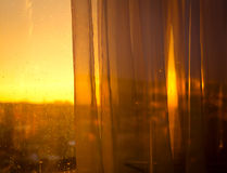 View the sunset from balcony through curtains Royalty Free Stock Image