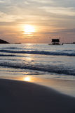 The view of the sunset and boats from the sandy beach. Stock Photo