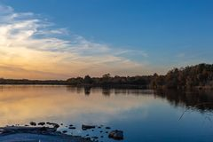 View of sunset with fall colors with reflections in the lake. View of sunset with fall colors at the lake edge with reflections in the water. Beautiful colors of stock images