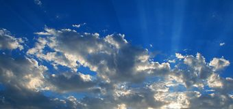 RADIATING CLOUDS AND LIGHT SHAFTS. View of sunset with glow on clouds and radiating beams of light Royalty Free Stock Image