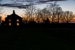 Sunset at Shaker Village of Pleasant Hill - Kentucky. A view of a sunset, with the lights of the West House illuminated, at the Shaker Village of Pleasant Hill Stock Images