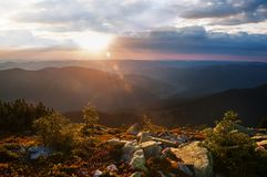 View of the sunset from the mountains in the distance. The dark silhouettes of the peaks of the mountains, huge blocks of moss-gro. Wn stones in the foreground stock image
