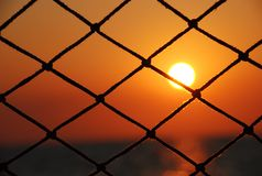 View of the sunset through the net of sailboat royalty free stock photo