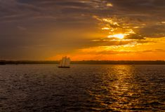 View of sunset in New York Harbor. Spectacular sunset view of New York Harbor with sailboat passing by New Jersey in background Stock Photo