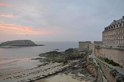 View at sunset from the wall of the old city with granite buildings of Saint-Malo in Brittany, France. Saint Malo beach, sea and sunset. View of red and blue stock photos