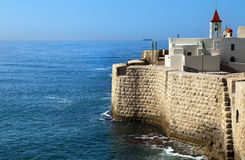 Old Town of Acco by the Sea. View at the surrounding wall of the old town of Acco (Acre) in Israel, bordering with the Mediterranean sea. The church on the right Royalty Free Stock Photos