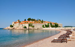 A view of the Sveti Stefan island on a summer day with beach and loungers, Montenegro. 2014 royalty free stock photo