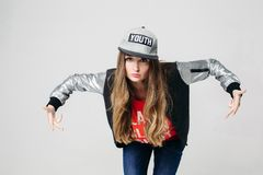 Swag stylish teenage girl in cap posing with hands up. stock photo
