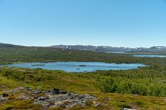 View of the Swedish highlands in summer sunshine. View of the Swedish highlands or fjeld world with mountain peaks and a small lake, on a beautiful summer day stock photo
