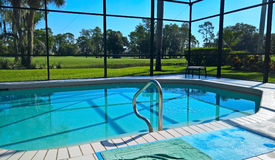 A view of the swimming pool in a house in Florida in the middle of Naples golf course with grass and palm trees under a blue sky Royalty Free Stock Photo