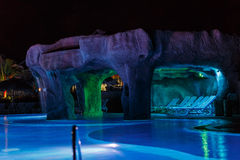View of swimming pool with various colorful beautiful lights and cozy warm grotto. Night view of swimming pool with various colorful beautiful lights and cozy Stock Photos