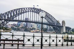 View of Sydney Harbour Bridge from the Circular Quay on a wet morning, with city in the distance and a ferry crossing over.  royalty free stock photo
