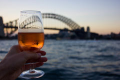 View of Sydney Harbour Bridge. A glass of rose wine with the Sydney Harbour Bridge in the background during sunset Royalty Free Stock Images