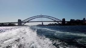 View of Sydney Harbour Bridge From Ferry, Australia. View of Sydney harbour Bridge and ship wake from fast ferry or boats traveling East along Harbour, Sydney stock video